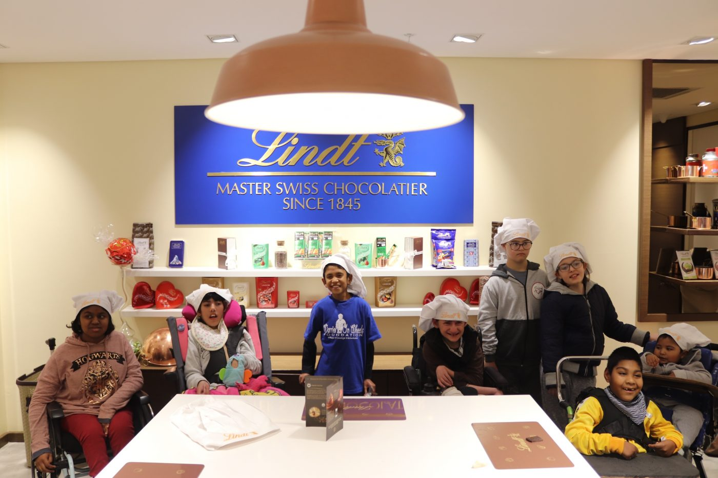 8 Children in front of the Lindt Chocolate Studio sign and stand